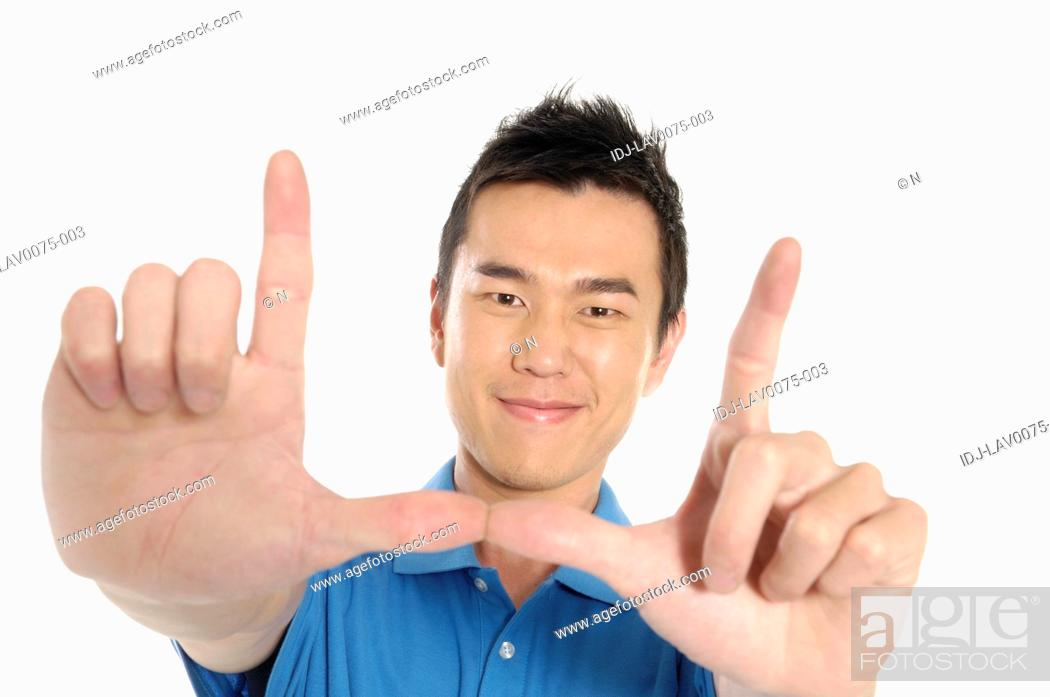 Stock Photo: Male university student making frame with fingers.