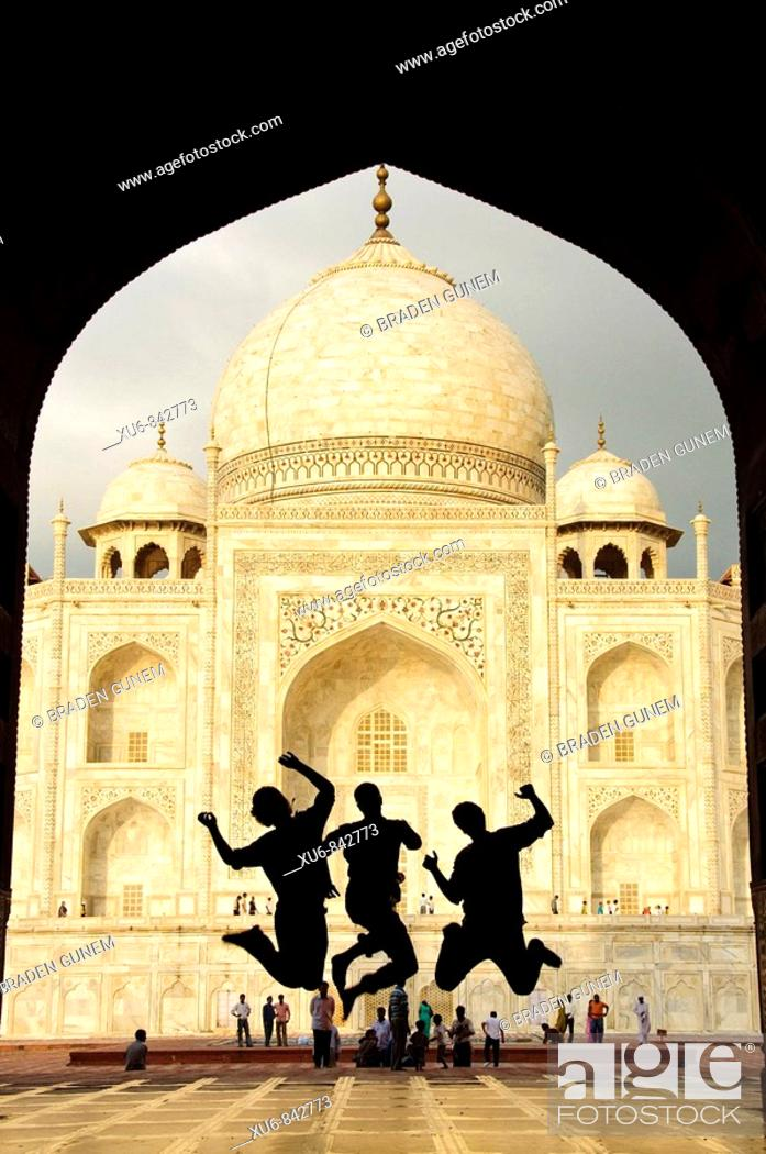 Photo de stock: Tourist teens jumping in front of the Taj Mahal Agra, India.