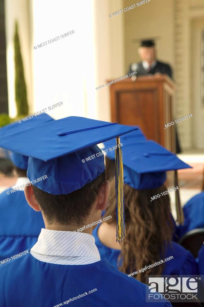 Stock Photo: Graduates listening to speaker outside back view.