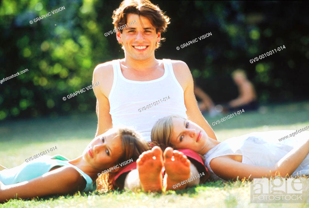 Stock Photo: Portrait of a young man with two young women lying on his lap.