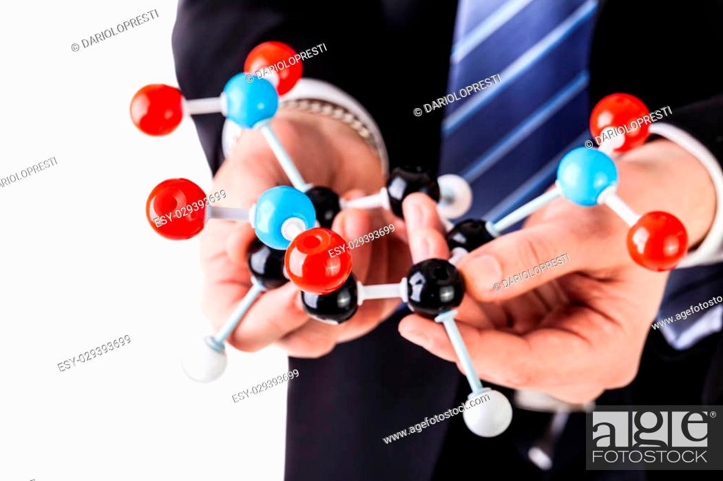 Stock Photo: a businessman wearing a suit and a tie holding a trinitrotoluene tnt molecular model isolated over white.