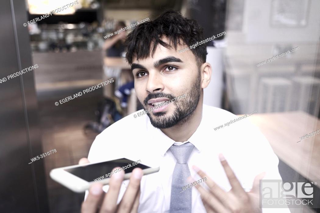Stock Photo: Businessman in cafe, explaining idea on phone.