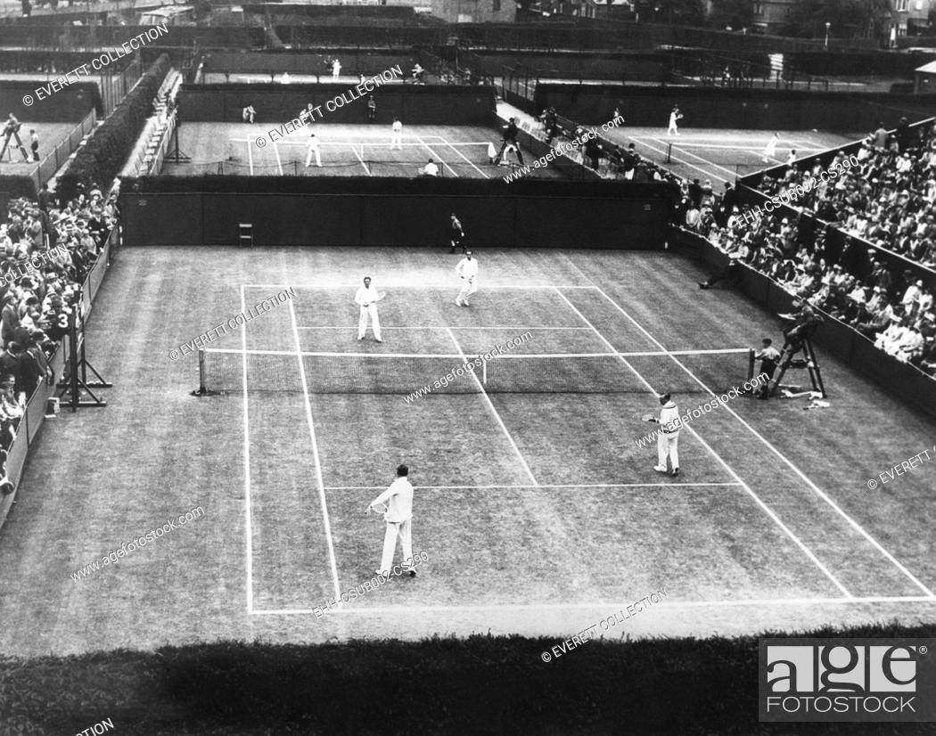 Stock Photo: English lawn tennis championship play at Wimbledon, July 2, 1930. In closest court, a double matches was played by Bill Tilden of the US.