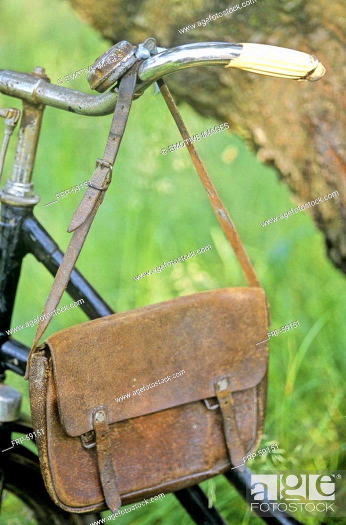 Stock Photo: Old leather bag hanging on bicycle handlebar.