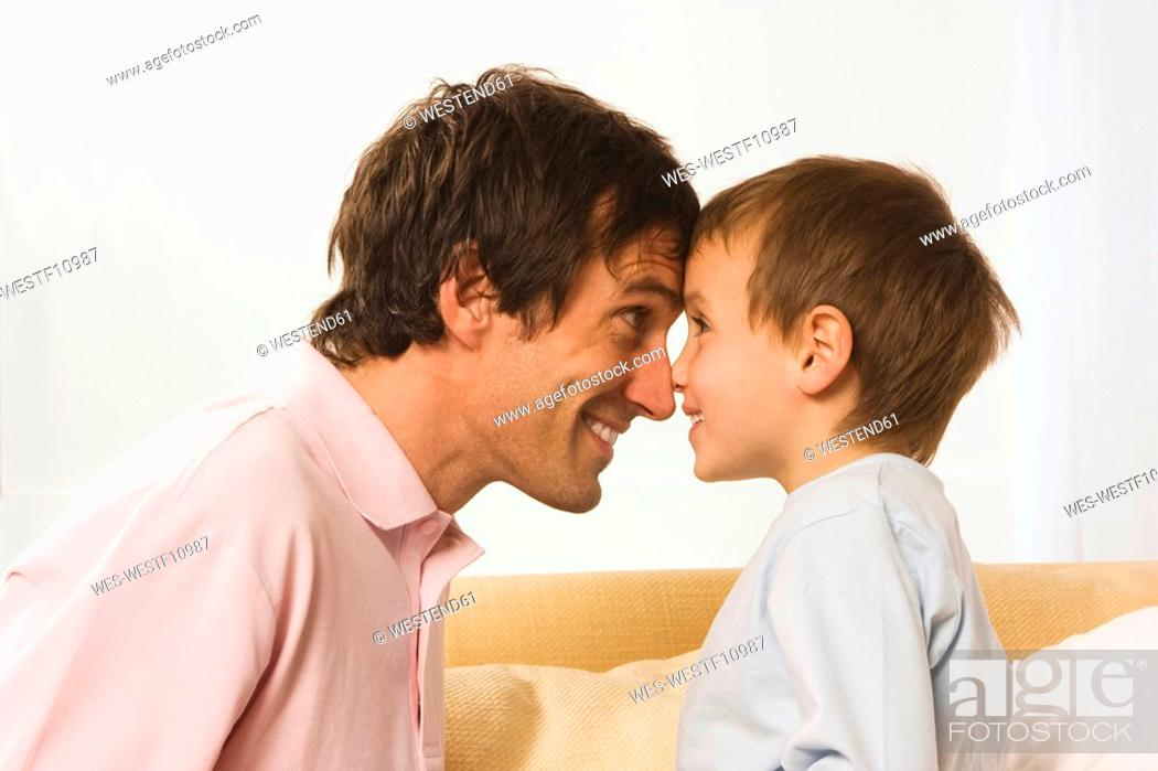 Stock Photo: Father and son 4-5, fooling about, head to head.