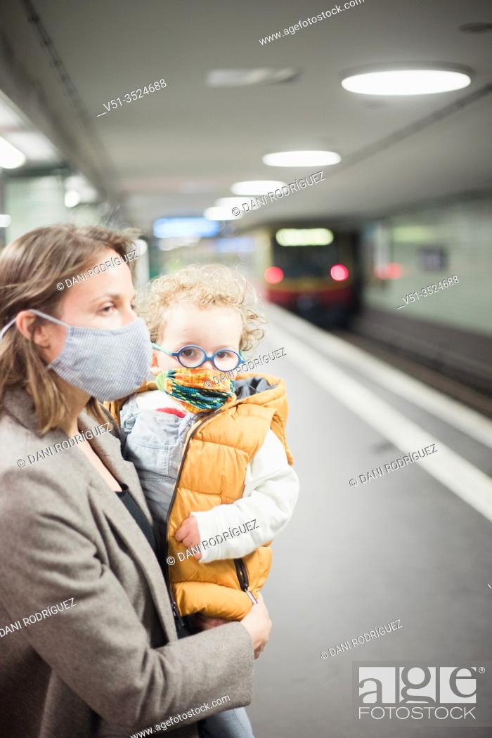 Stock Photo: Mother and son taking public transportation with mask during Corona days.