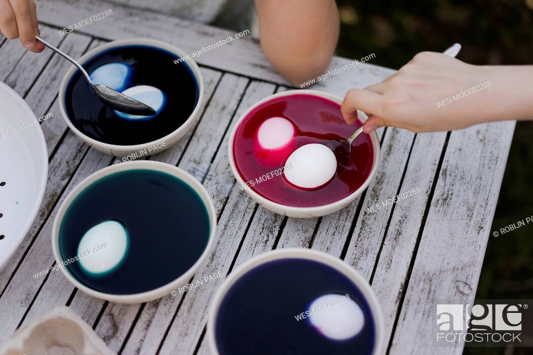 Photo de stock: Close-up of two girls dyeing Easter eggs in garden.