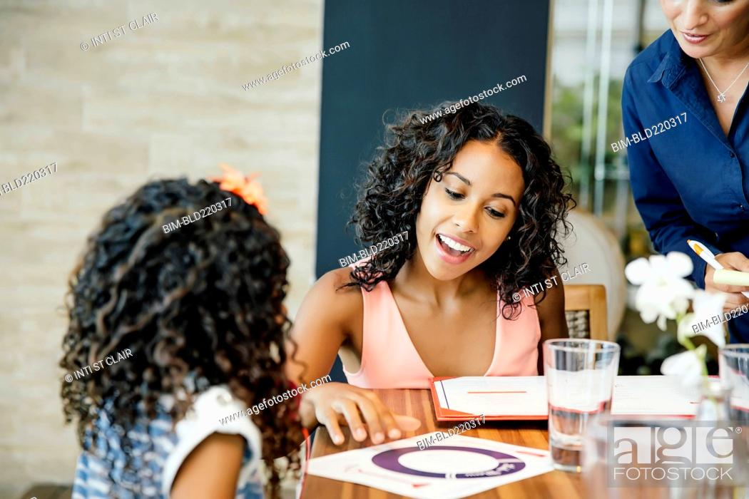 Stock Photo: Mother and daughter reading menu restaurant table.