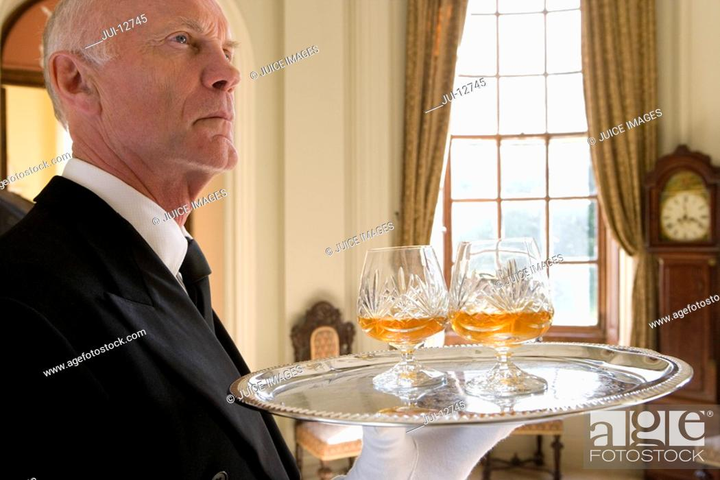 Stock Photo: Butler with tray of drinks, low angle view.
