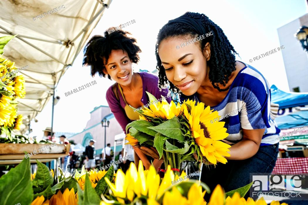 Stock Photo: Women shopping together at flower stand.