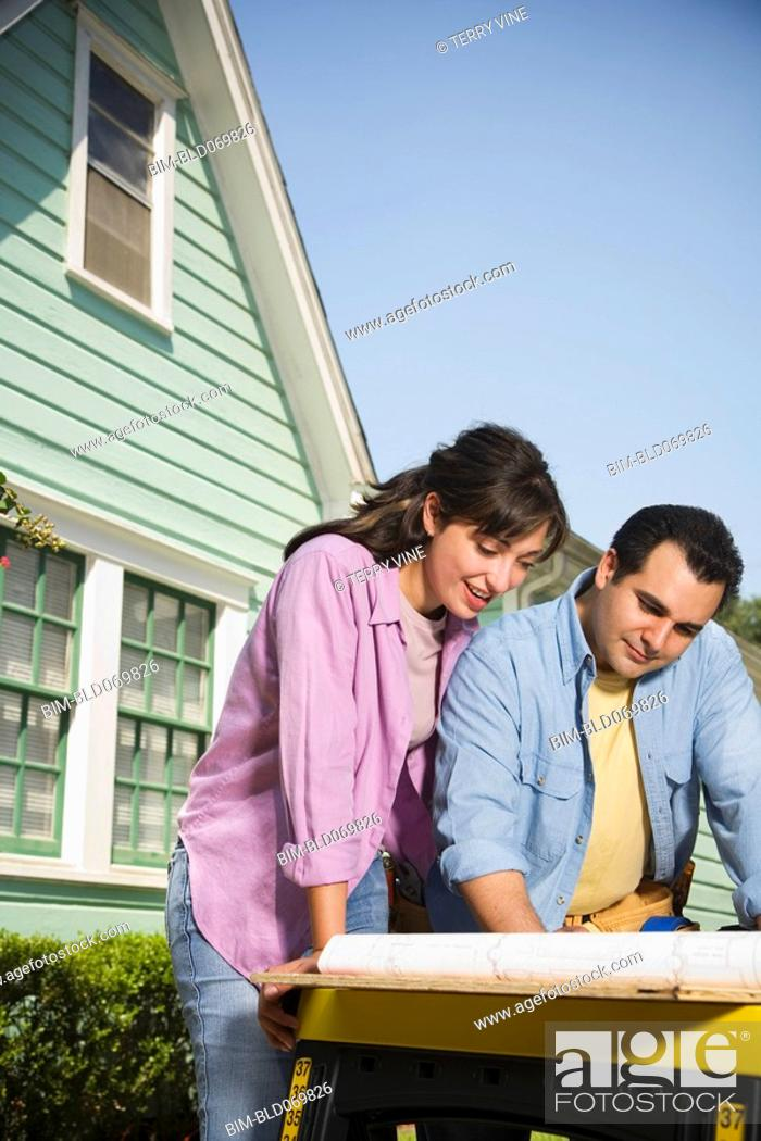 Stock Photo: Hispanic couple looking at blueprints outdoors.