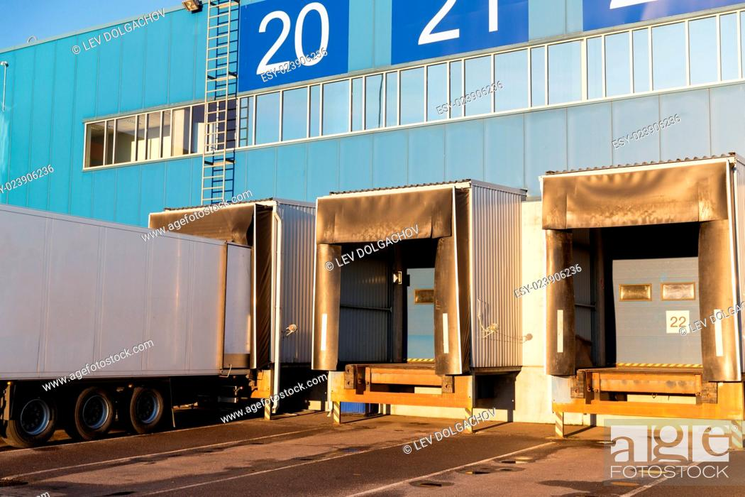 Stock Photo: logistic, storage, shipment, transportation and loading concept - warehouse gates and truck loading.