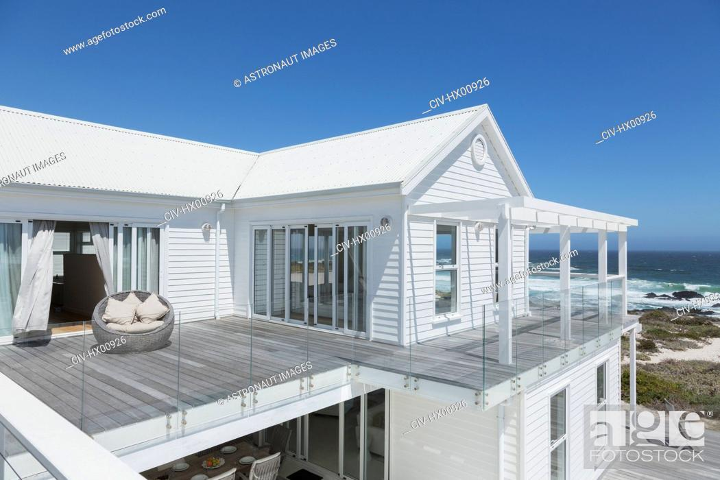 Stock Photo: White beach house with balcony with ocean view under sunny blue sky.