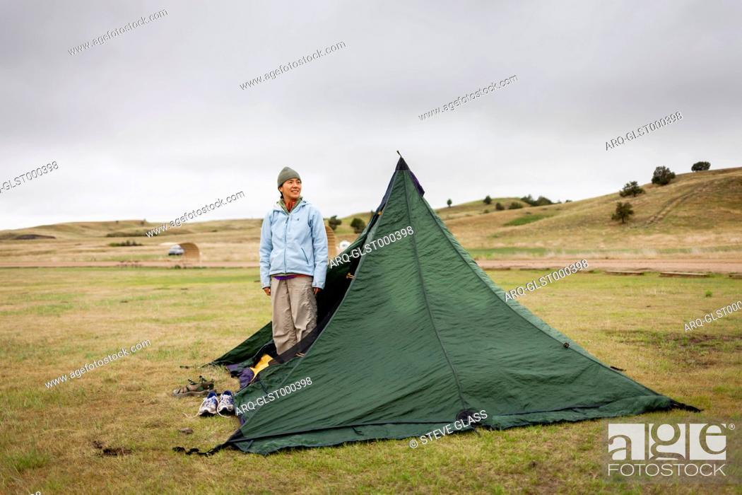 Stock Photo: A Japanese American woman stands in her tent after a night of rain and surveys the land in the primitive campsite, Sage Creek Campground, Badlands National Park.