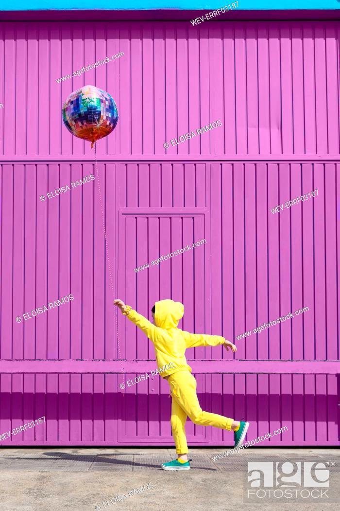Stock Photo: Children dressed in yellow standing in front of purple garage door holding balloon.