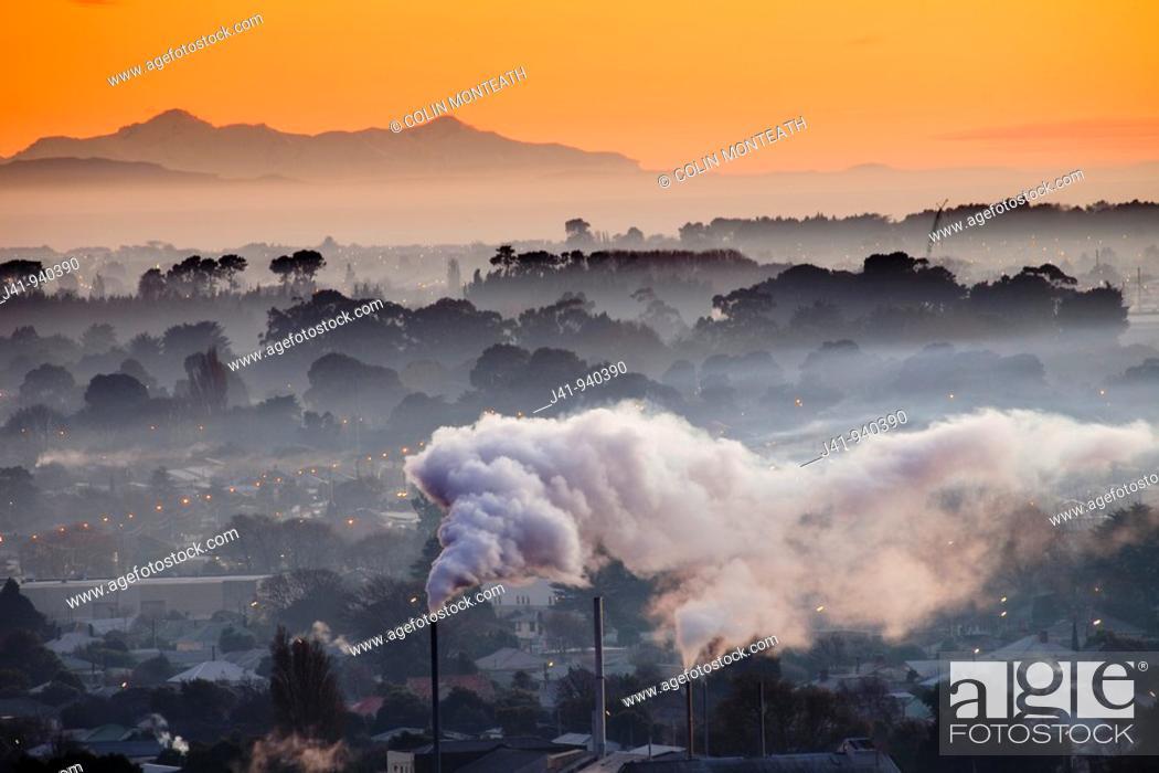 Stock Photo: Winter dawn over industrial chimneys, Christchurch, Seaward Kaikoura range behind, New Zealand.