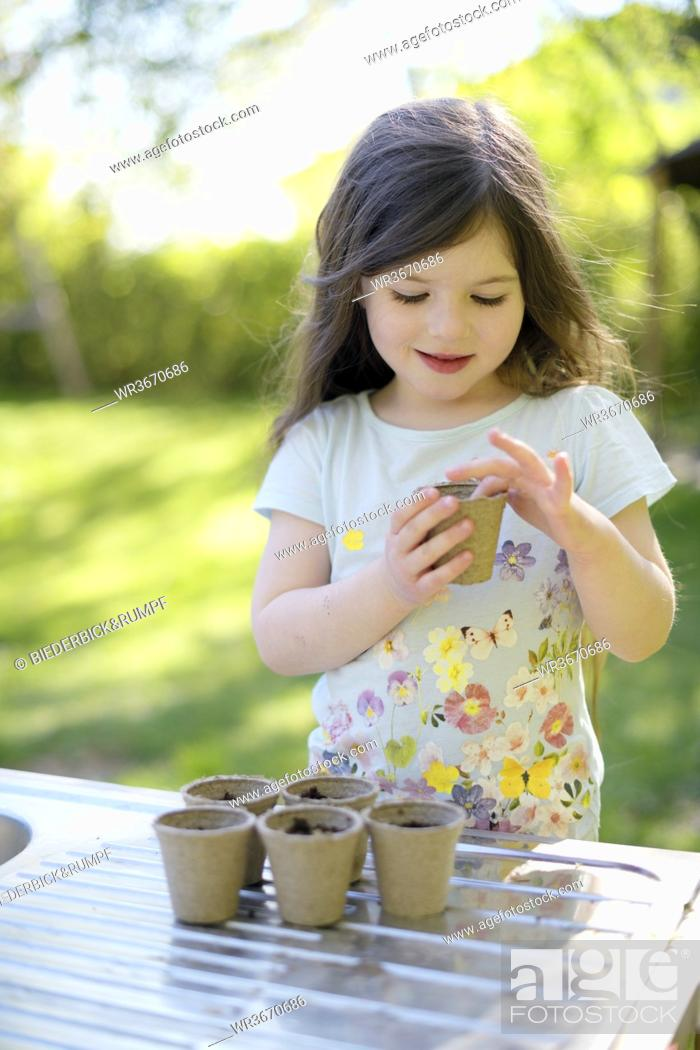 Stock Photo: Cute girl planting seeds in small pots on table at garden.