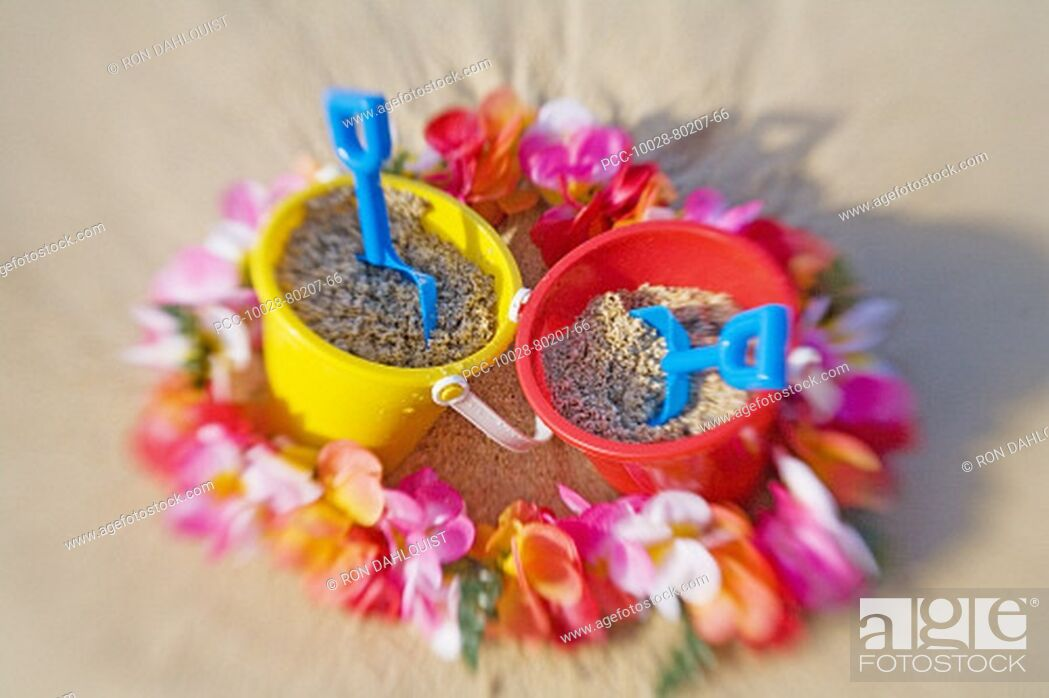 Stock Photo: Two sets of brightly colored shovel and pails surrounded by a lei on a sandy beach.