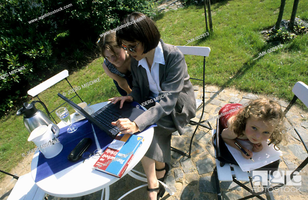 Stock Photo: A woman, businesswoman, mother, 40-45 45-50 years old, sitting at the table in the summerly garden, working at the laptop and a two girls, 1-5 5-10 years old.