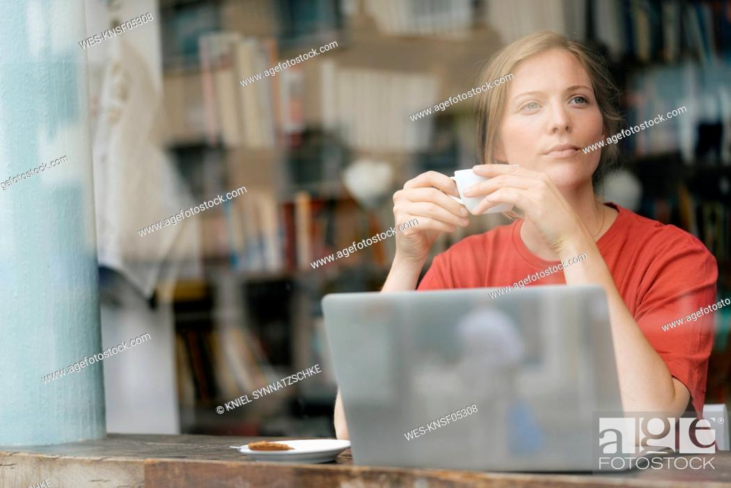 Stock Photo: Young woman with cup of coffee and laptop in a cafe.