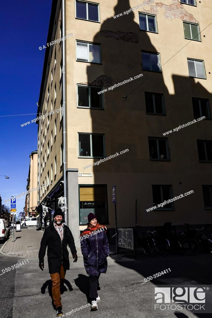 Imagen: Stockholm, Sweden April 1, 2020 Pedestrians on the corner of Timmermansgatan and Bengt Ekehjelmsgatan on Sodermalm and the shadow of a classic building.