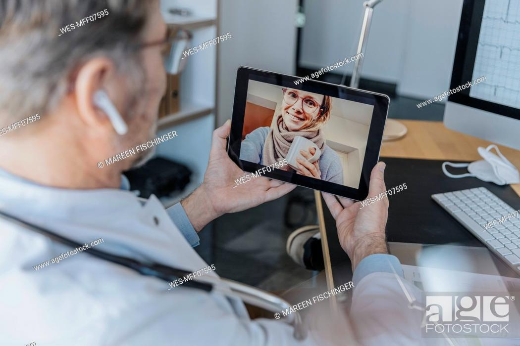 Stock Photo: Male healthcare worker talking to patient over digital tablet while sitting at doctor's office.