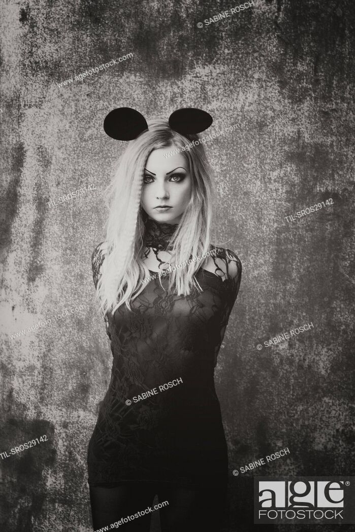 Stock Photo: black-white photo of young woman with blonde hair wearing a black lace dress and wearing mouse ears wearing a heart ring.