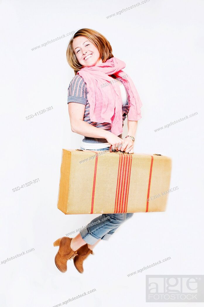Imagen: Young woman with suitcase jumping.