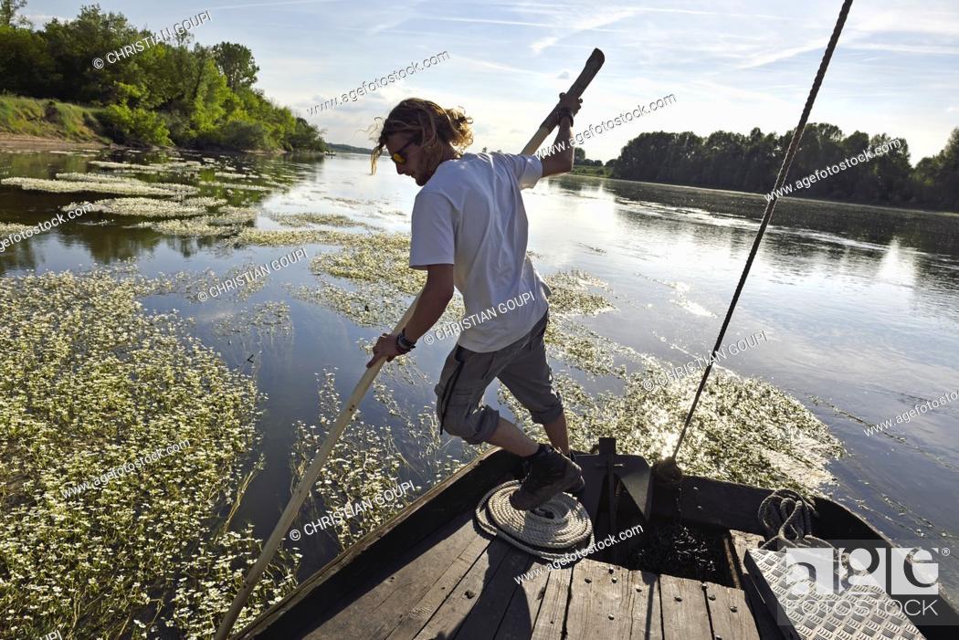 Imagen: pilote degageant le bateau des bancs de renoncules des rivieres (Ranunculus fluitans), Balade en toue sur la Loire aux environs de Chaumont-sur-Loire.