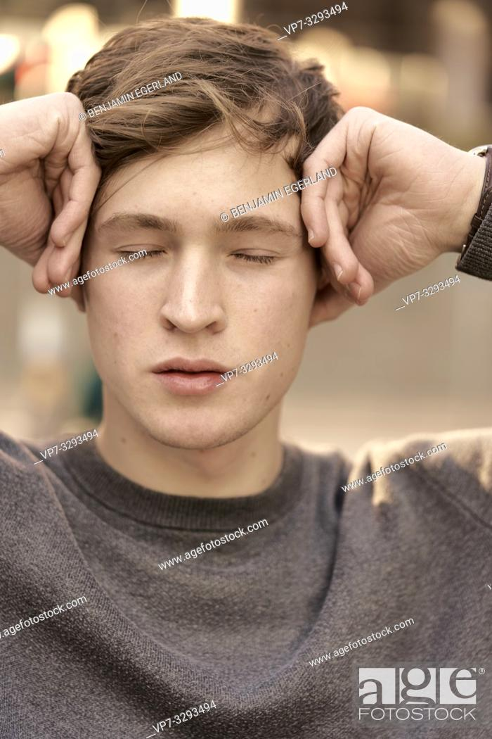 Stock Photo: young model man, closed eyes, pressing hands on temporal, in Hamburg, Germany.