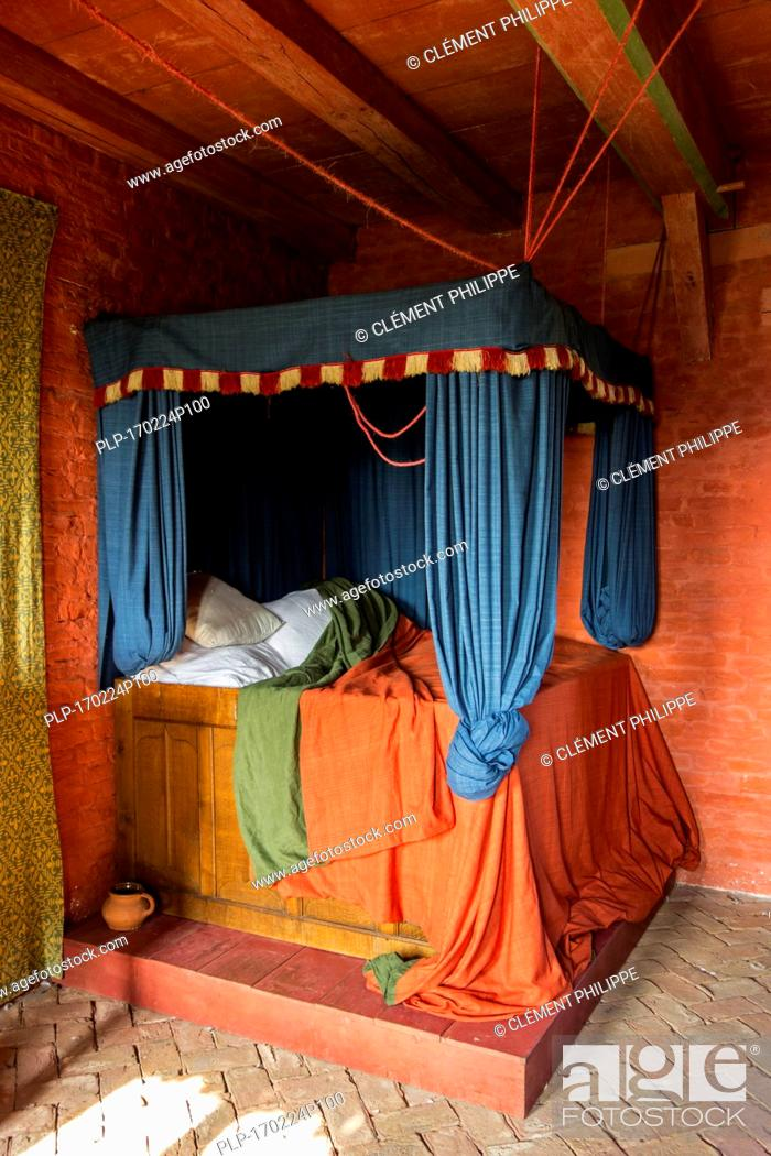 colourful medieval curtained bedstead bed with curtains in bedroom