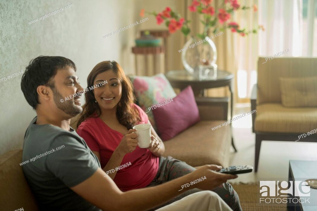 Stock Photo: Man holding Television remote and woman with coffee on sofa.