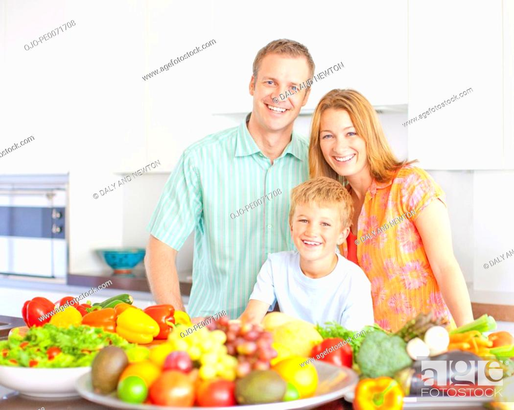 Stock Photo: Family in kitchen with fruits and vegetables.