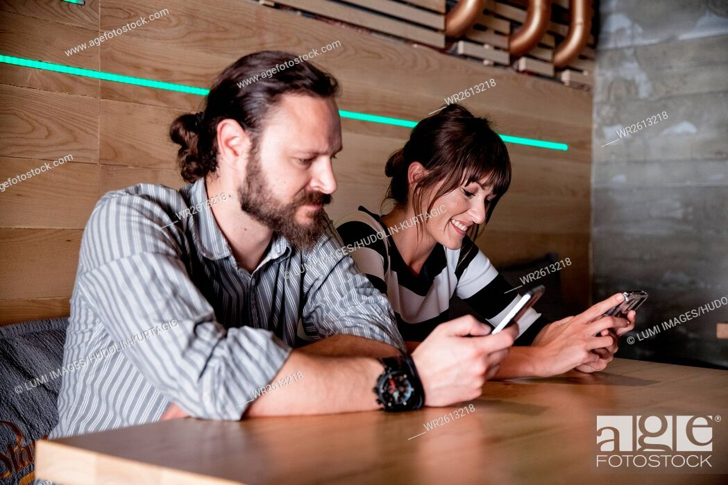 Imagen: Couple in coffee shop looking at their smartphones.