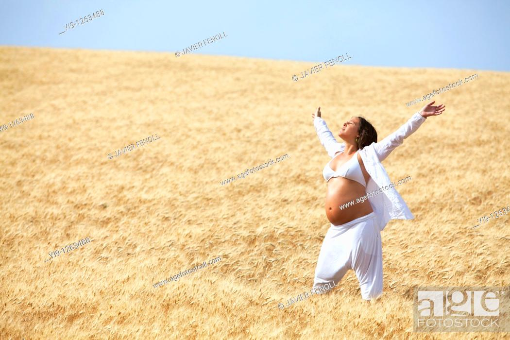 Stock Photo: Pregnant woman relaxing in field.