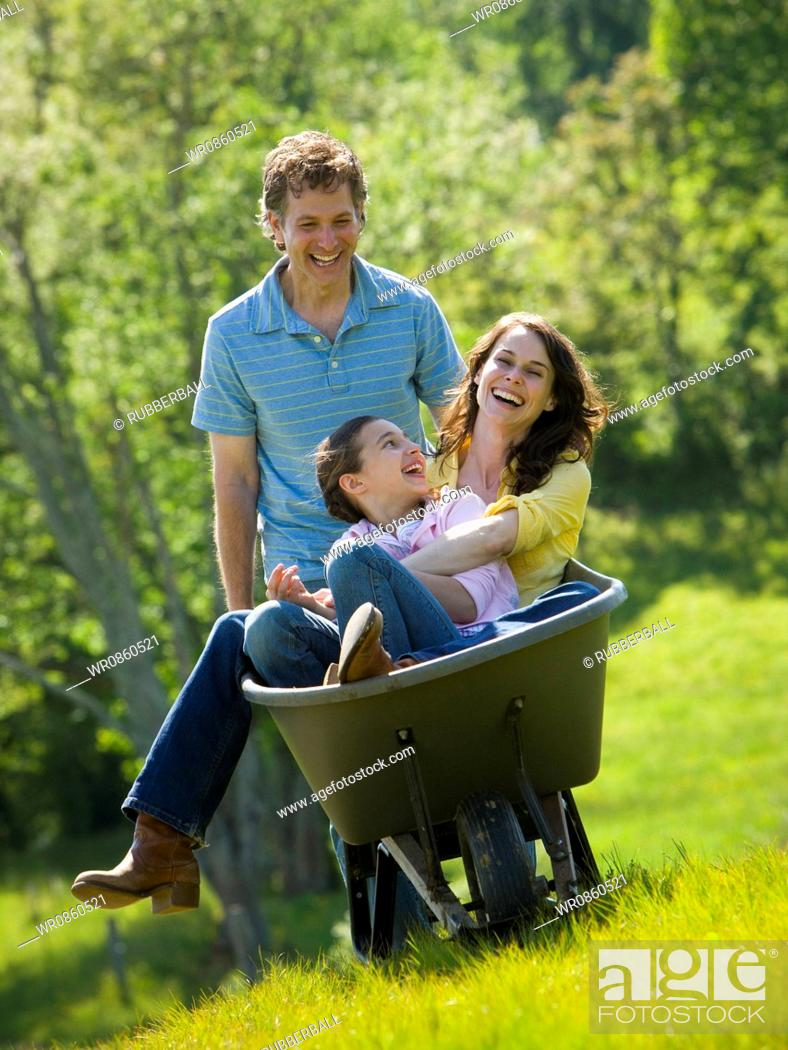 Stock Photo: woman and her daughter sitting in a wheel barrow with a man standing beside them.