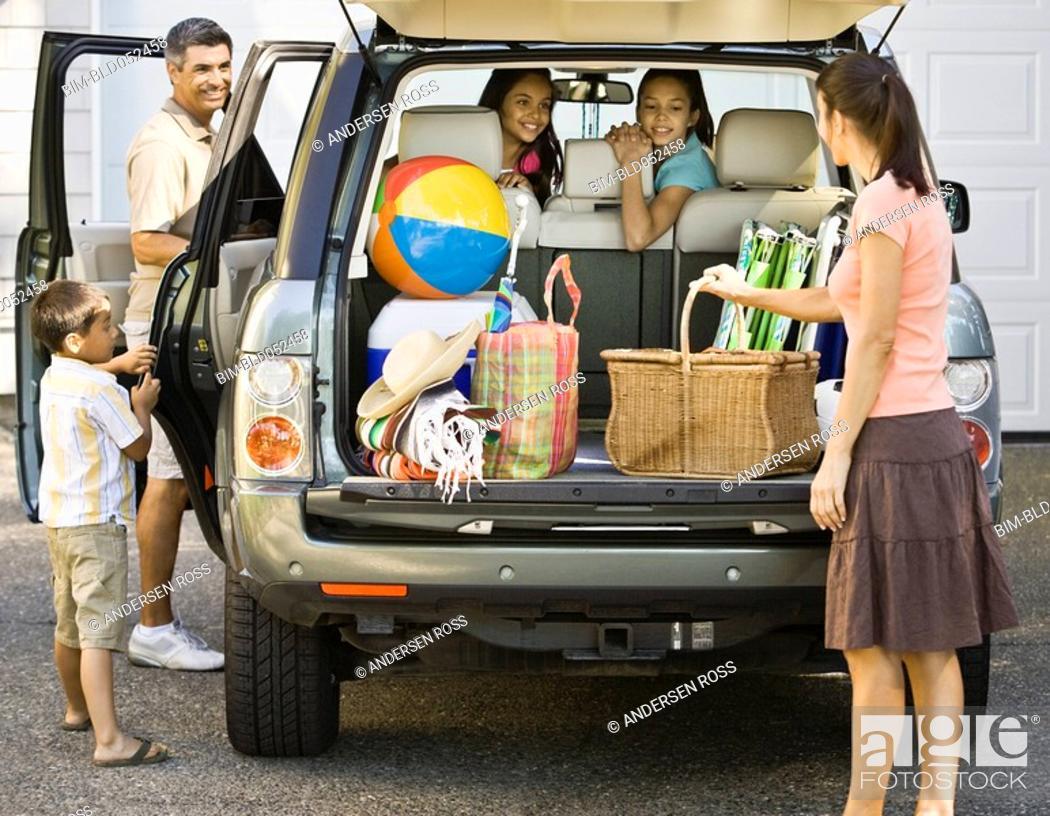 Stock Photo: Hispanic family loading car for trip.