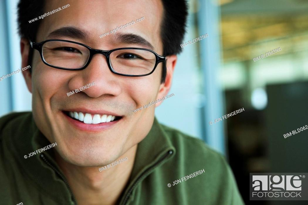 Stock Photo: Close up of Asian American man wearing eyeglasses and smiling.