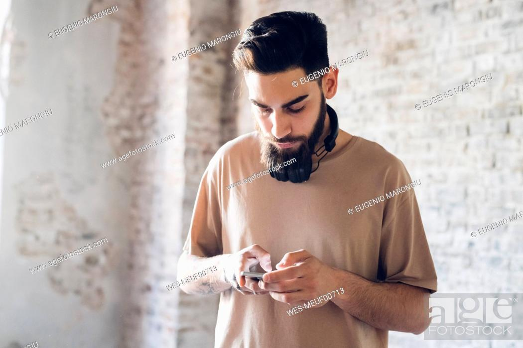Stock Photo: Stylish young man using smartphone in loft.