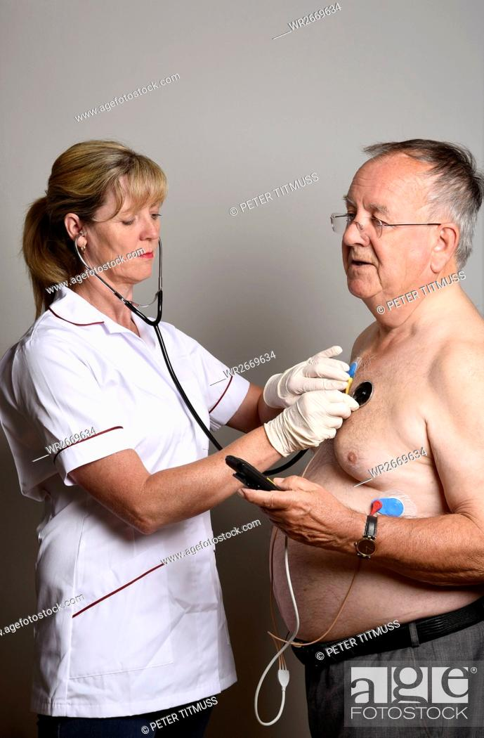 Stock Photo: England Uk Member of a Hospial Cardiac Measurement Team Installing A Ambulatory Ecg Monitor To An Overweight Male Patient.