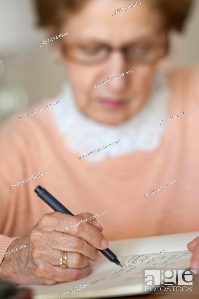 Stock Photo: Detail of a senior woman writing in a note book.