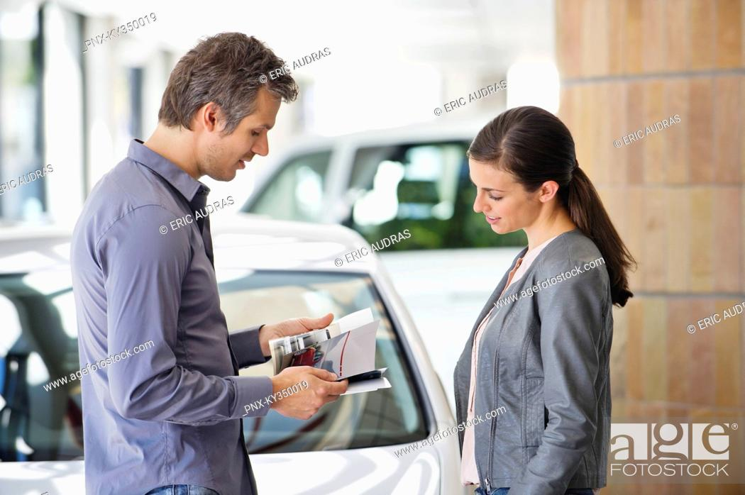 Stock Photo: Side profile of a couple looking at catalog in car showroom.