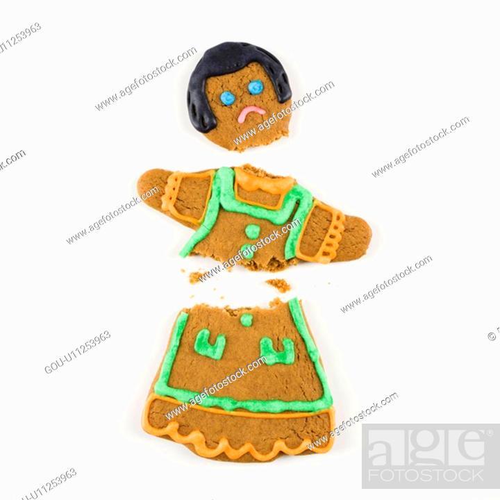 Stock Photo: Frowning female gingerbread cookie broken in half.