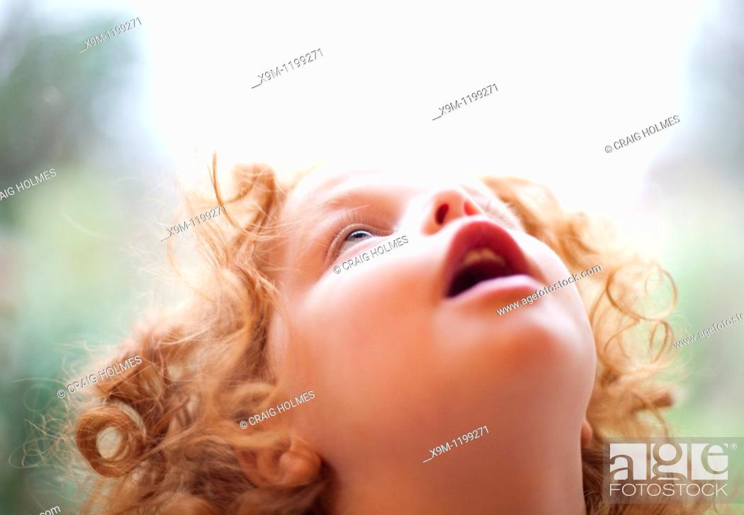 Stock Photo: A three year old girl looking in awe at the sky above.