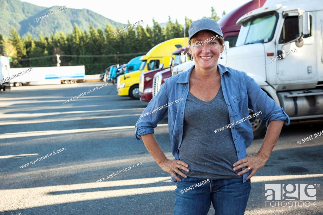 Stock Photo: A Caucasian woman truck driver near her truck parked in a parking lot of a truck stop.