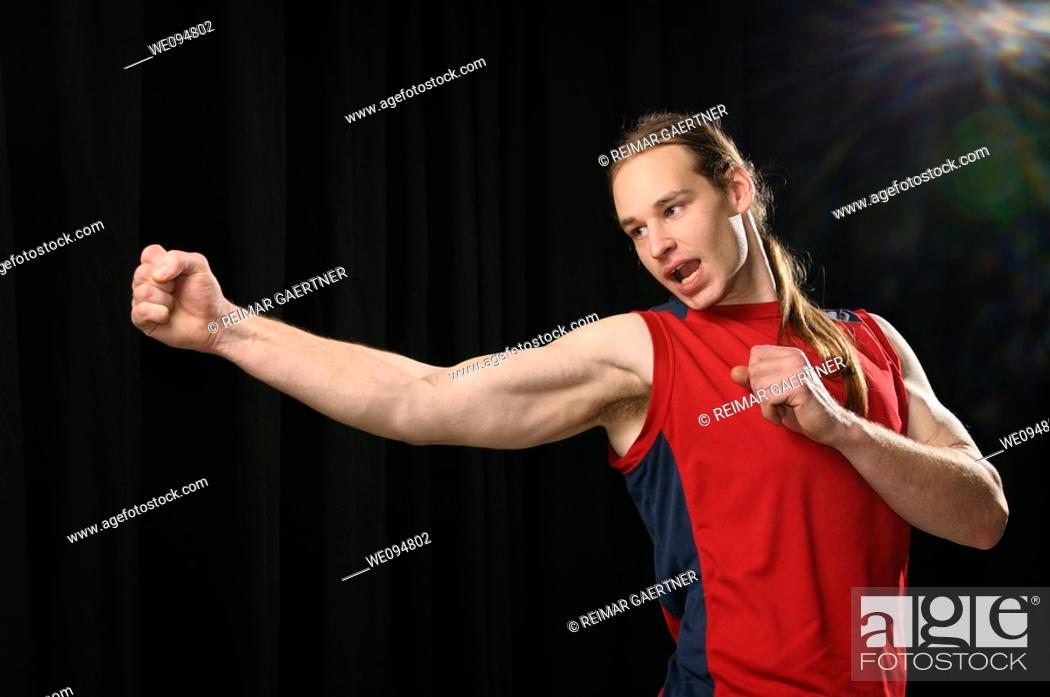 Stock Photo: Young male with long hair practicing a swivel Karate punch while yelling in spotlight.