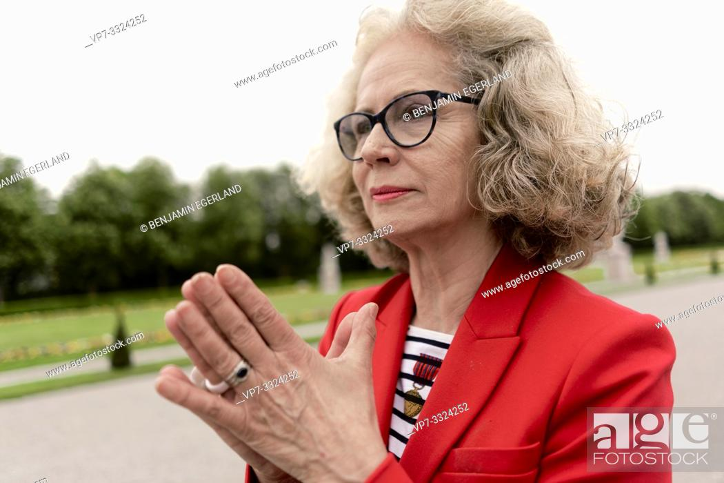 Stock Photo: senior woman (67 years old) with folded hands in park, in Nymphenburg, Munich, Germany.