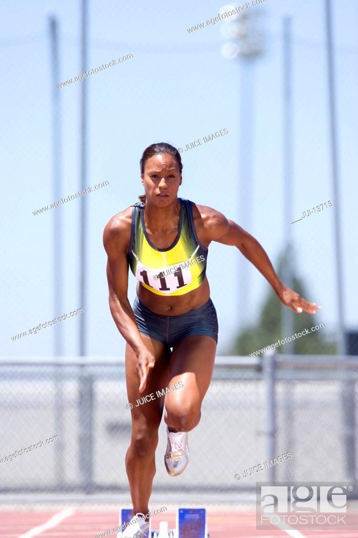 Stock Photo: African female runner leaving starting block.