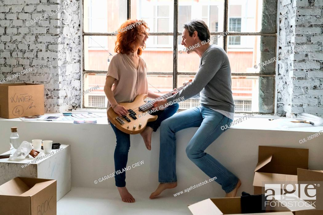 Imagen: Couple moving into industrial style apartment, sitting on window ledge with guitar.