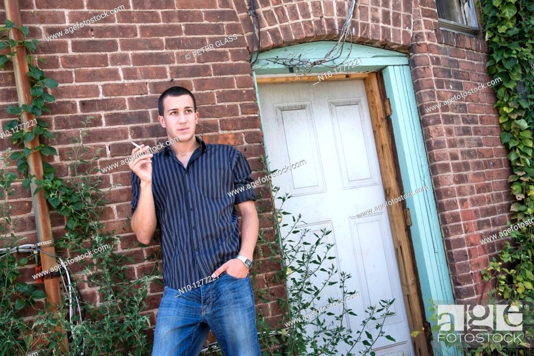 Stock Photo: Young man, smoking, standing by his apartment door.